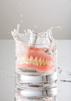 artificial Teeth splashing on water glass